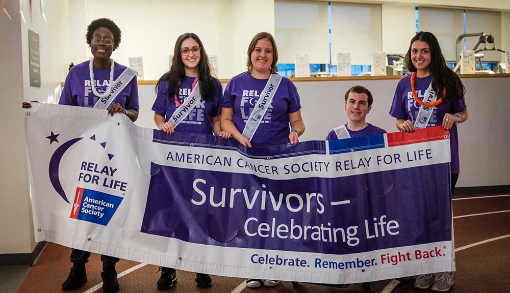 "Cancer survivors carry a ""Survivors--Celebrating Life"" banner around the indoor track during Relay for Life."