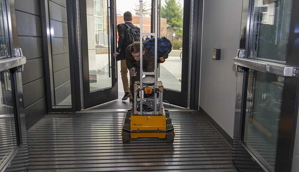 Two students pull their robotic project out the door of the Foisie Innovation Studio.
