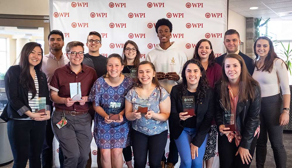Recipients of student achievement awards pose with their awards in front of a WPI banner.