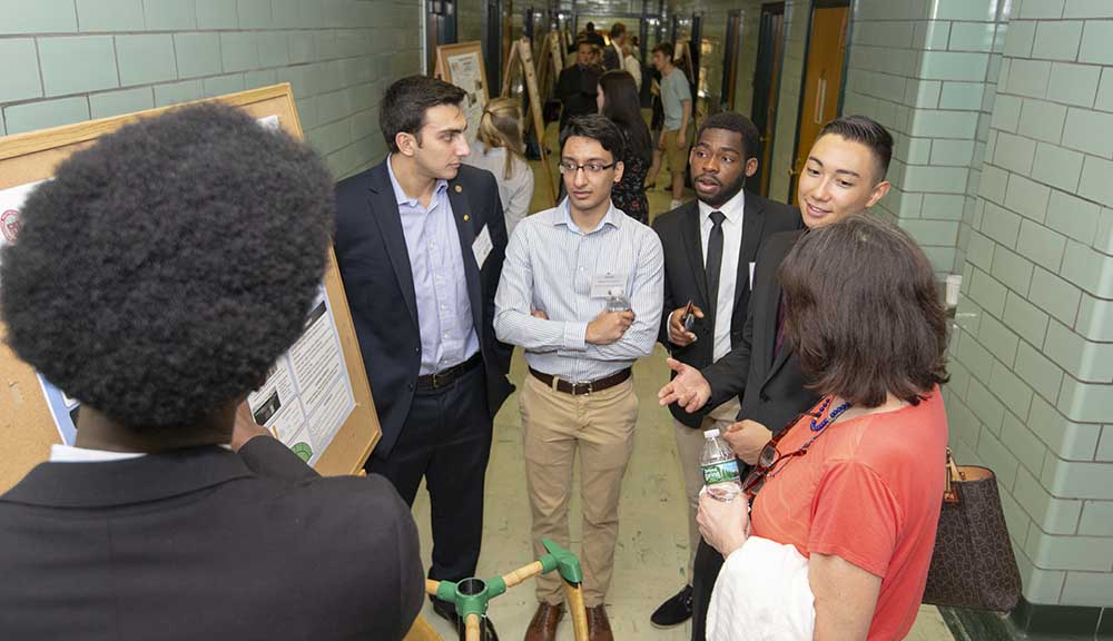 Students explain their work to a Project Presentation Day attendee.