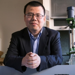 Yan Wang leaning against a lab bench and looking into the camera