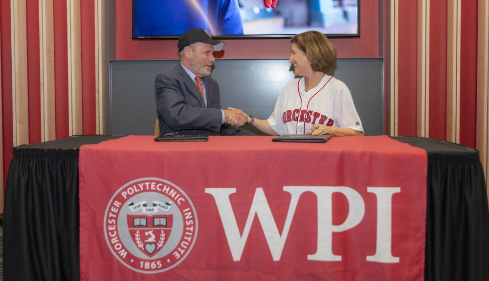 Larry Lucchino shakes hands with Laurie Leshin at a table with a WPI logo on it as they make the WPI/Red Sox partnership official.
