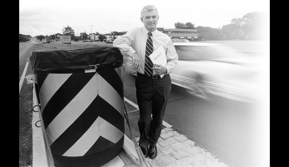 Former WPI Provost Jack Carney poses with a large crash cushion designed to protect cars striking a concrete highway median barrier