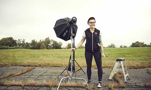Doreen Manning stands next to a light stand for a photoshoot. She's smiling and is wearing a black vest over a white shirt, glasses, and a hat.
