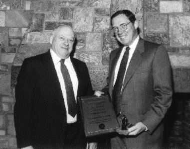 Willam Grogan, left, and Allaire, both in suites. Alaire holds an award plaque alt