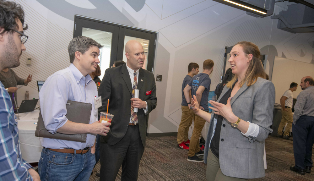 Ashley Lutz '19 (MS bioinformatics) chats with Geoff Bush (brother of TAN advisor Joe Bush '04) and David Pula, director of development in University Advancement.