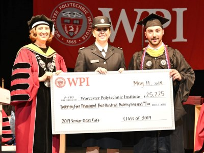 President Leshin, Rosie McCarthy (in unifiorm), and Lucan Mancinelli hold a large check alt