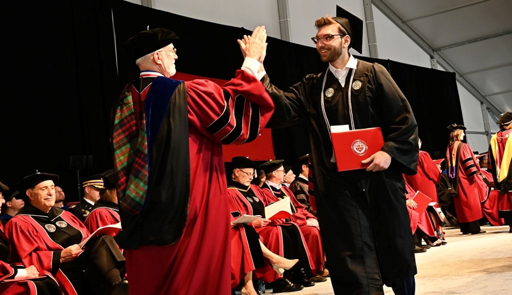 A graduate in cap and gown receives a high five from Arthur Heinricher, also in cap and gown