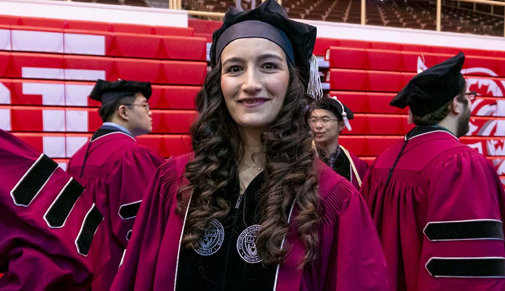 Wearing her graduation cap and gown, Gizem Selcan Cetin smiles in Harrington Auditorium.