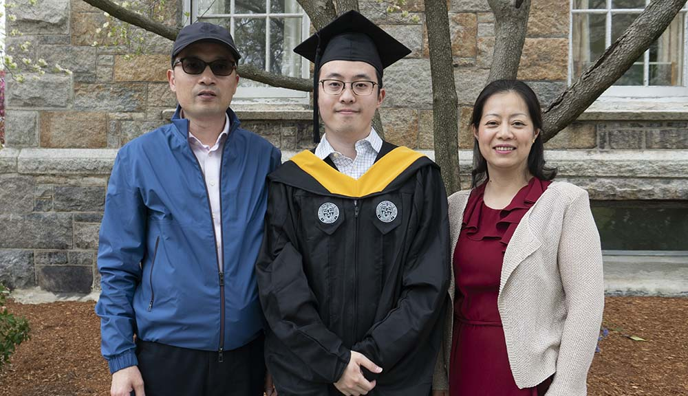 Haoyu Chen is dressed in his cap and gown and stands in front of Boynton Hall with his parents.