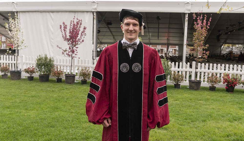 Wearing his cap and PhD robes, Kyle Dunn smiles in front of the Commencement tent on the Quad.