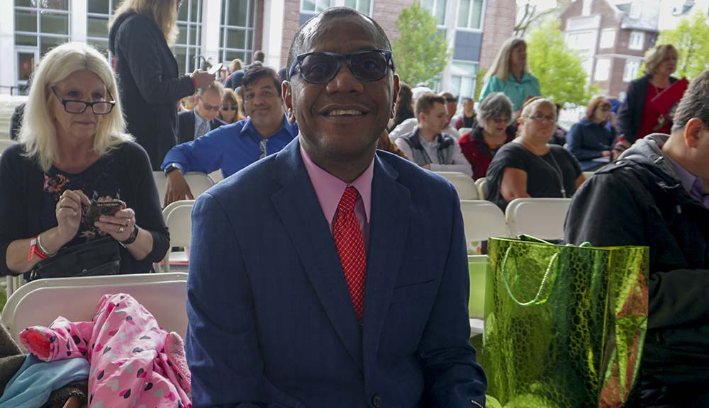 Ruthven Ottey sits under the Commencement tent on the quad, smiling. He's wearing a suit and sunglasses.