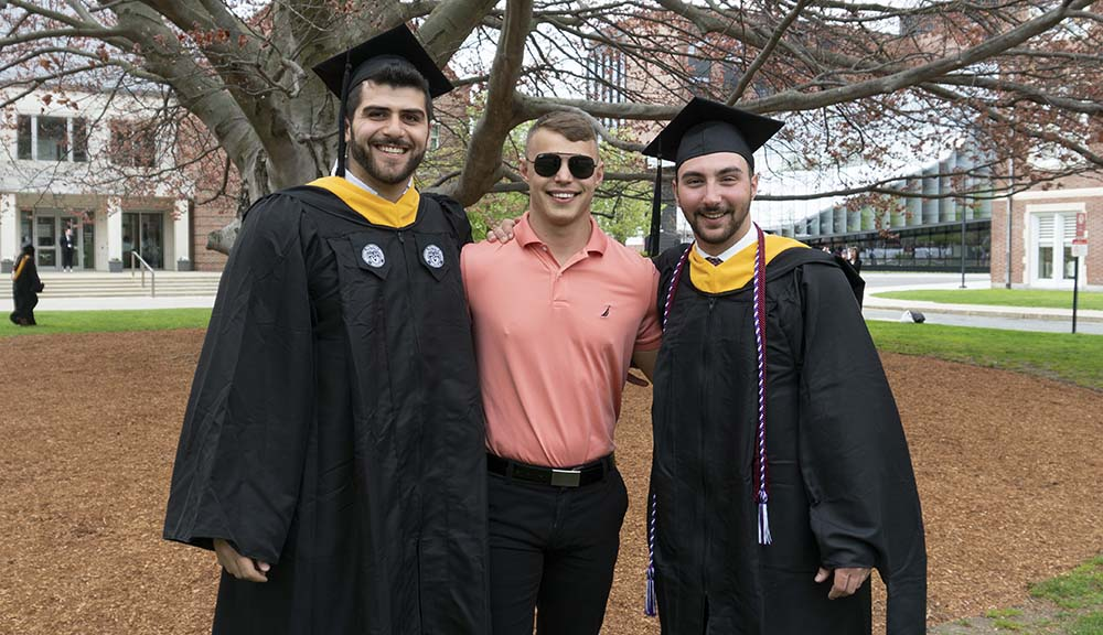 Three students, two wearing caps and gowns and one wearing sunglasses and a salmon-colored dress shirt, smile together in front of the beech tree.
