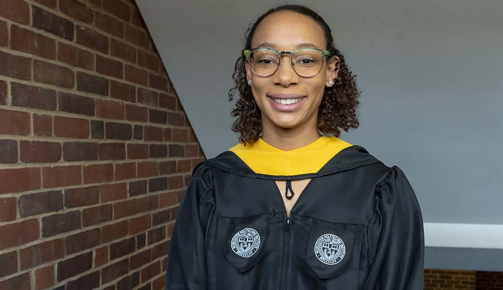 Wearing her graduation robes, Allysa Grant smiles in one of the brick hallways of Harrington Auditorium.