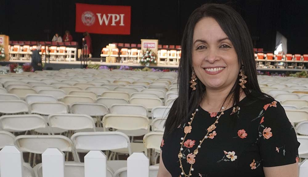 Lillian Caraballo smiles in front of the Commencement stage under the tent. A WPI banner is hanging behind her on the stage.
