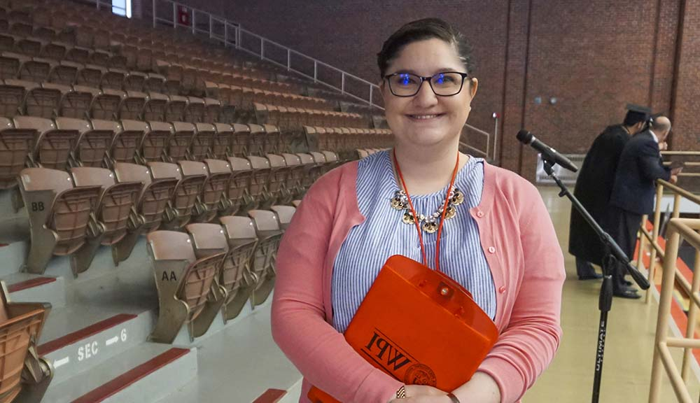 Holding a copy of the Commencement program, Maggie Becker smiles in Harrington Auditorium. She's wearing glasses, a light-colored shirt, and pink cardigan.