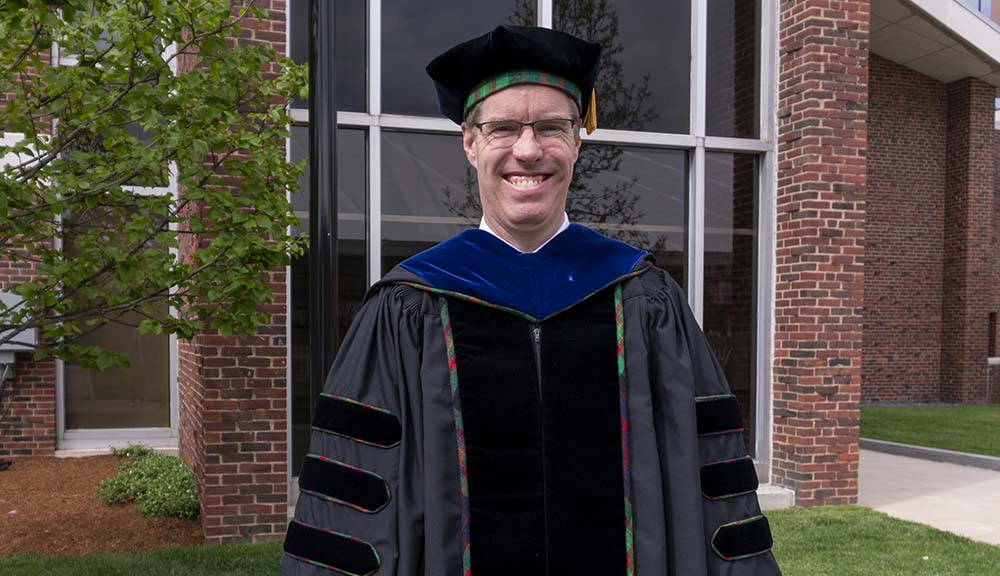 Wearing his faculty Commencement robes, Neil Heffernan smiles in front of Harrington Auditorium.