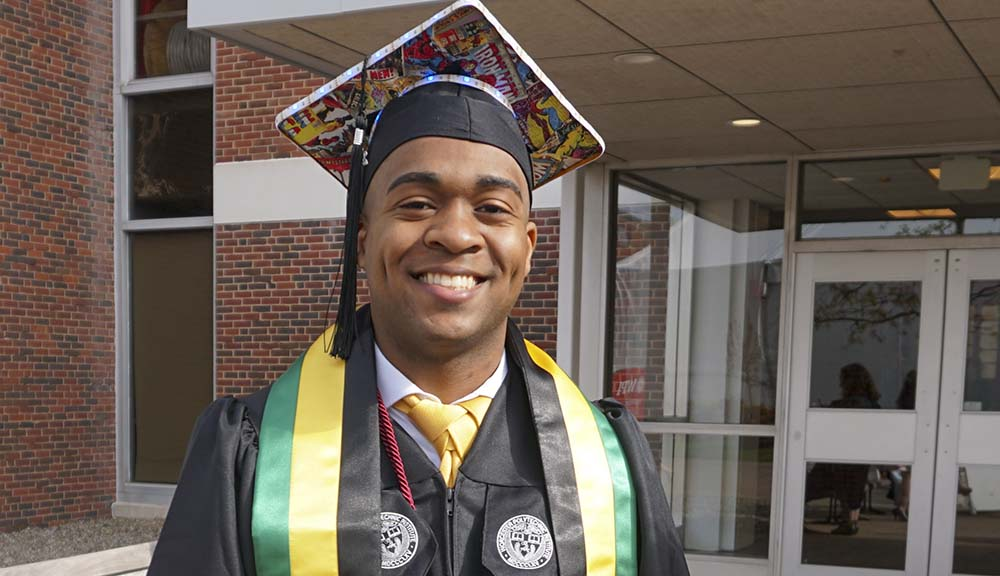 Wearing his decorated graduation cap and gown, Peter Ross smiles in front of Harrington Auditorium.