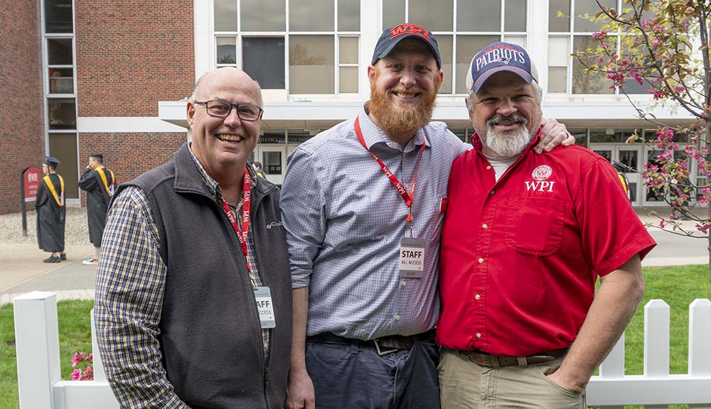 Three members of the facilities team smile together in front of Harrington Auditorium.