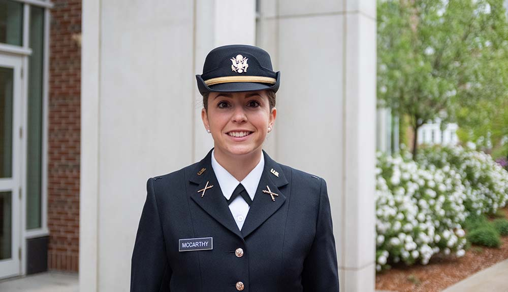 Rosie McCarthy, wearing her Army uniform, smiles in front of the Bartlett Center before the ROTC Commissioning Ceremony.