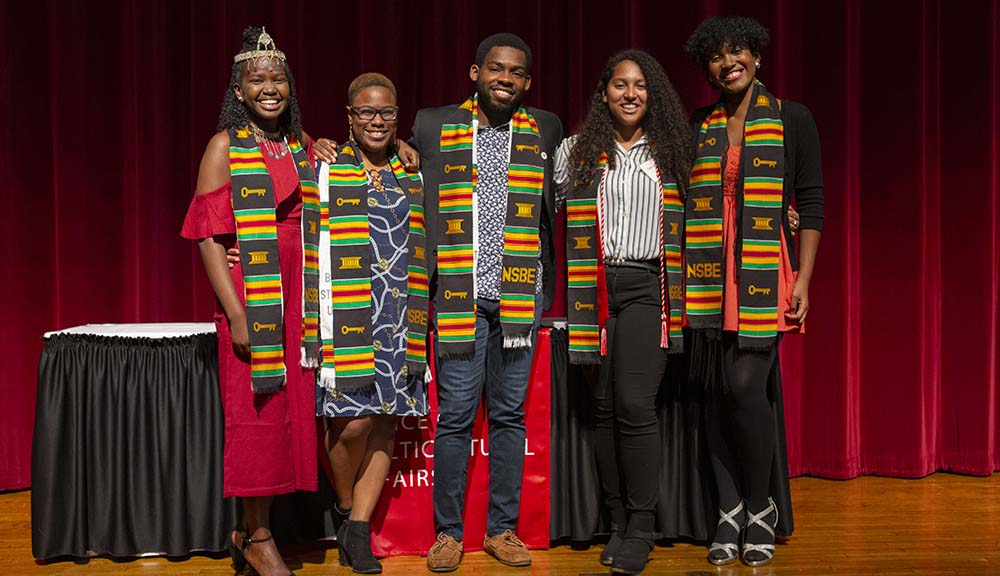 Students gather on the stage and smile for a photo during the Multicultural Commencement Ceremony.