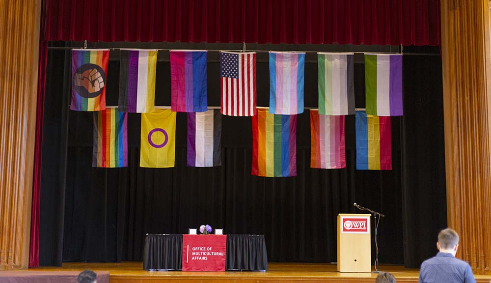 Various pride flags are displayed above the stage in Alden Memorial as part of the Lavender Commencement Celebration.