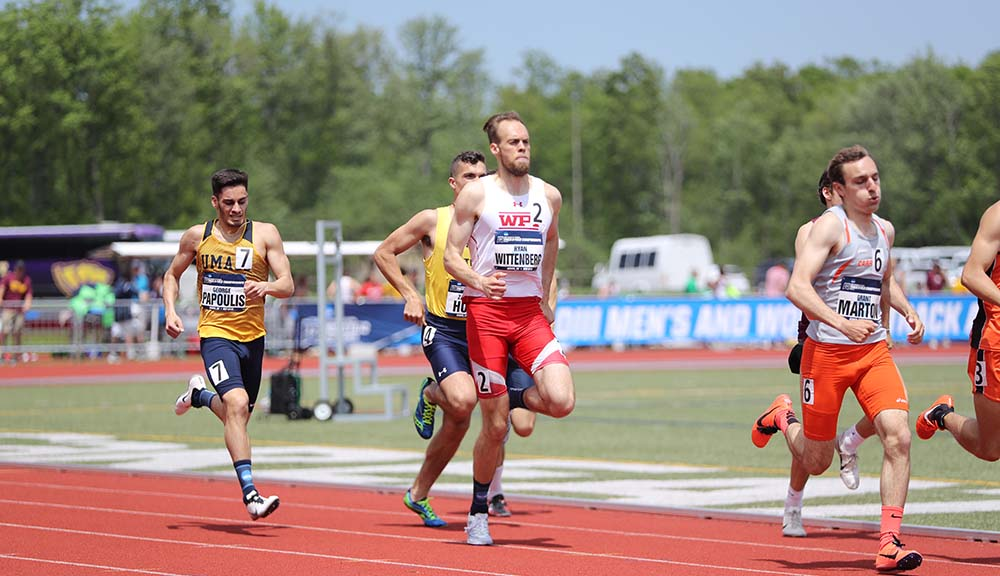 Ryan Wittenberg runs past students from other schools on the track.