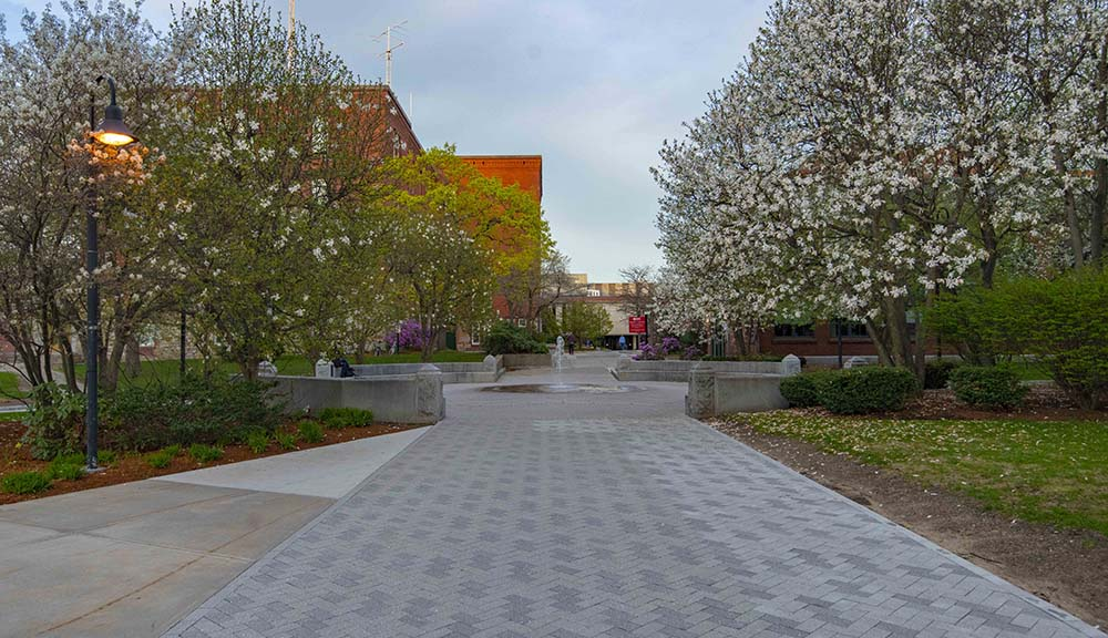 A beauty photo of the middle of campus surrounded by trees and flowers.