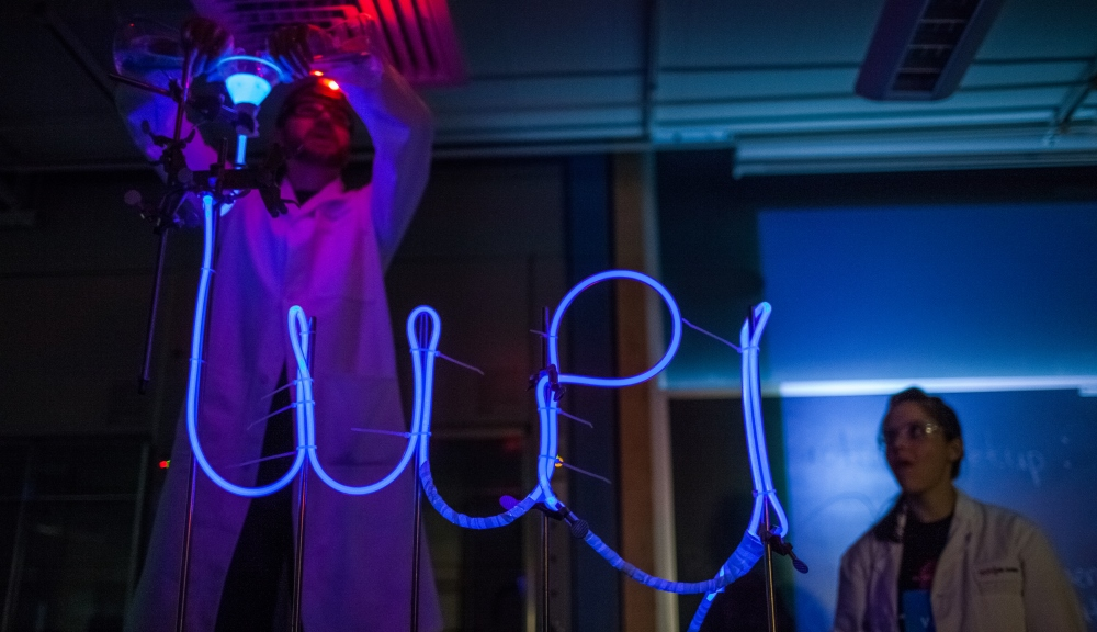 In a darkened lab, a scientist pours a glowing liquid into a tube that spells out WPI