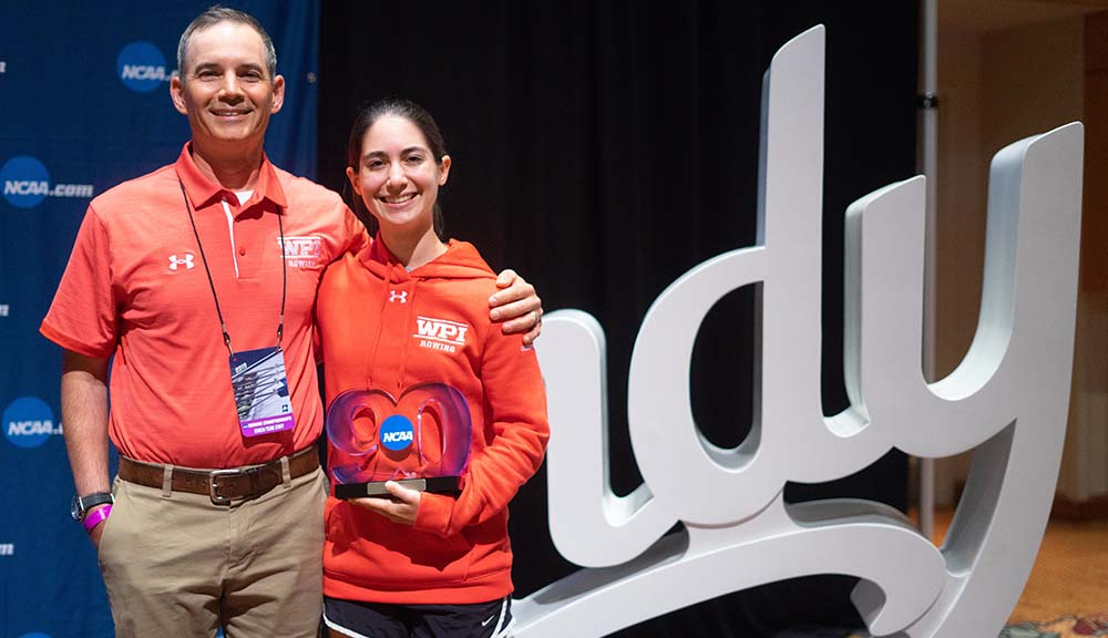 Head women's rowing coach Jason Steele and Sarah St. Pierre together at the awards ceremony. They're both wearing red WPI rowing gear and smiling, and Sarah is holding a trophy.