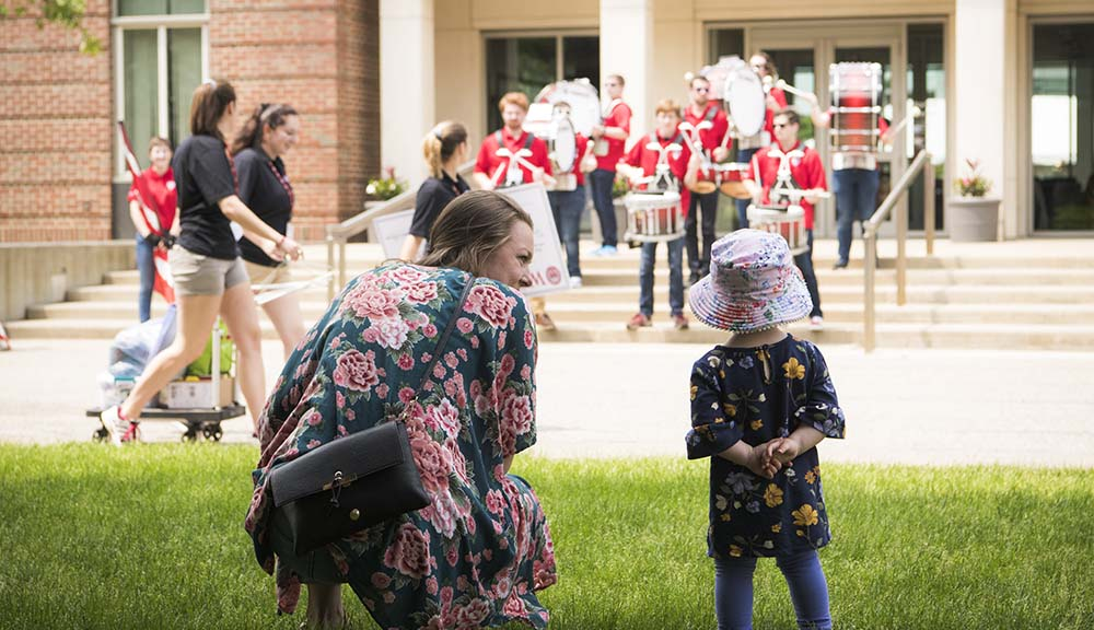 A mother and her young daughter watch members of the WPI Pep Band perform outside of the Bartlett Center from under the shade of the beech tree.