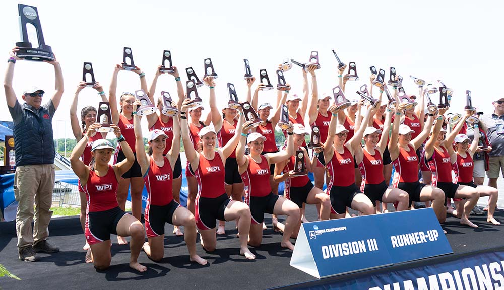 Members of the women's rowing team hold their trophies high in celebration.