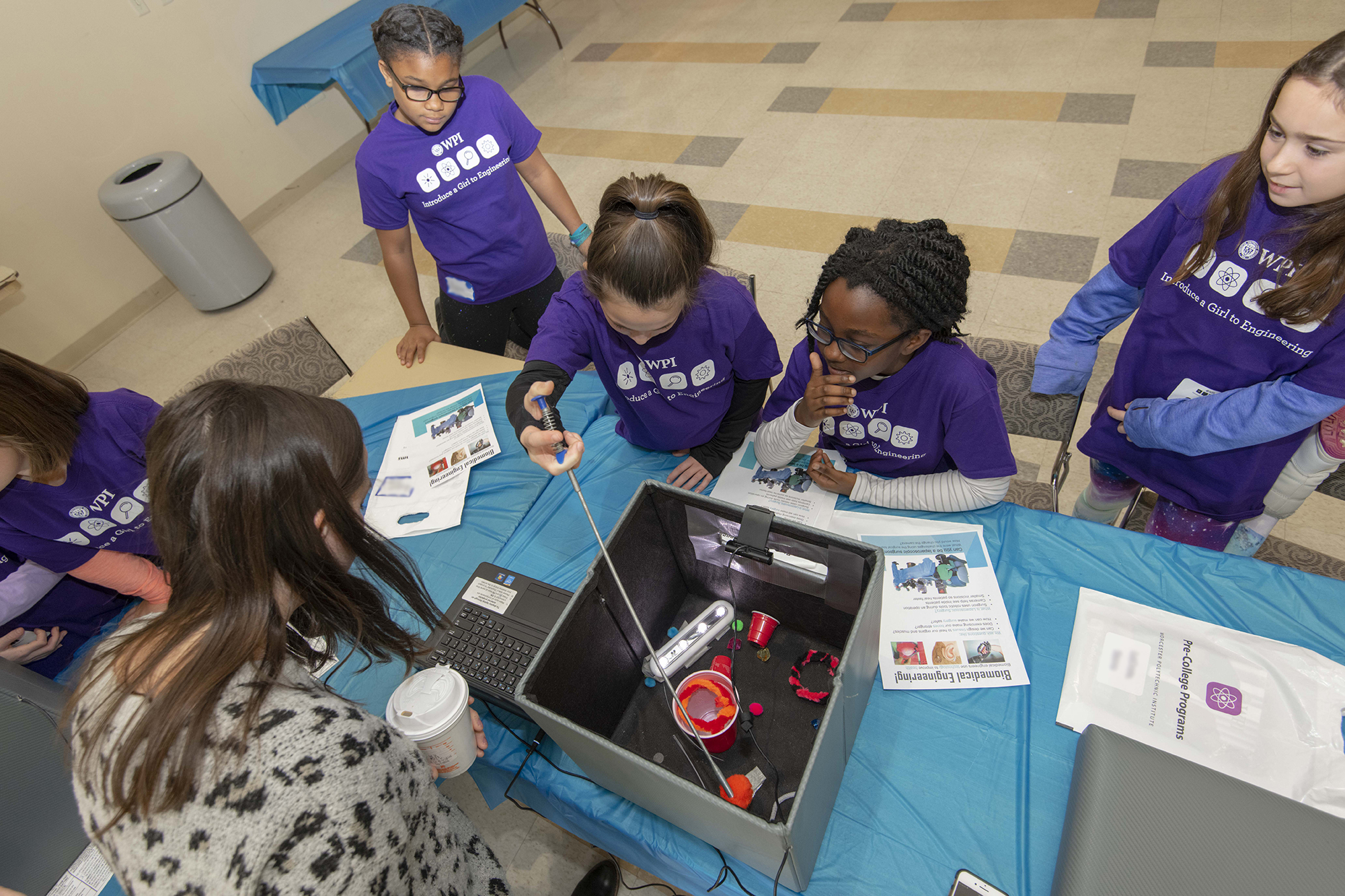 Group of girls at a table playing with an experiment related to Biomedical Engineering