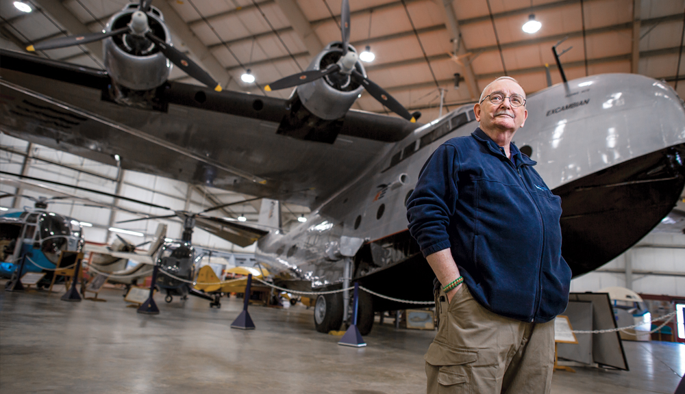 Mort Gutman standing in front of a large plane in a hangar.