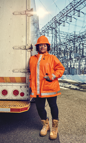 Wilkins standing next to the back of a truck outside of an electrical grid plant