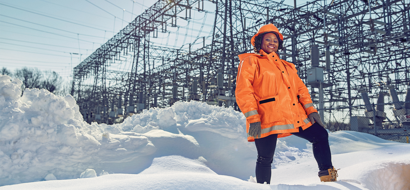 Wilkins standing on a pile of snow in front of an electrical grid plant outdoors.