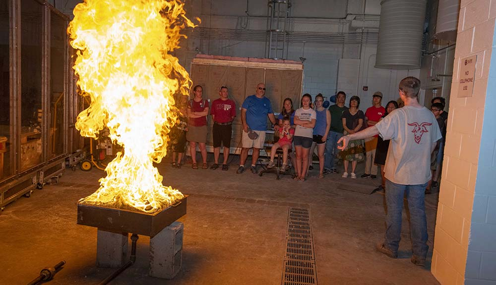 Attendees watch as a pillar of fire shoots up in the Fire Protection Engineering Lab.