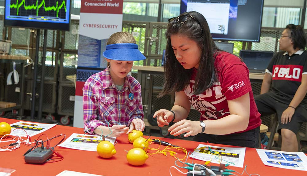 A TouchTomorrow volunteer assists an attendee with an experiment involving lemons and electricity.