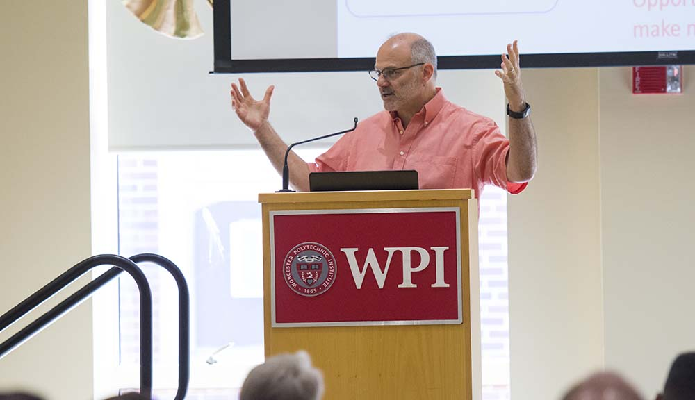Randy Bass stands at a WPI podium and addresses attendees of the Institute on Project-Based Learning.