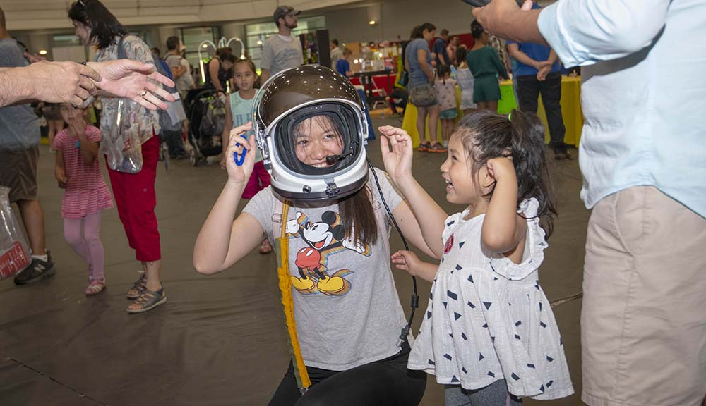 A TouchTomorrow attendee laughs while trying on an astronaut helmet.