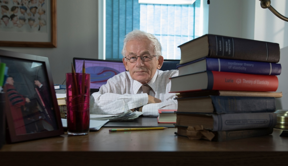 Professor Lurie at his desk with a stack of books to the lest and a frames photo to the right