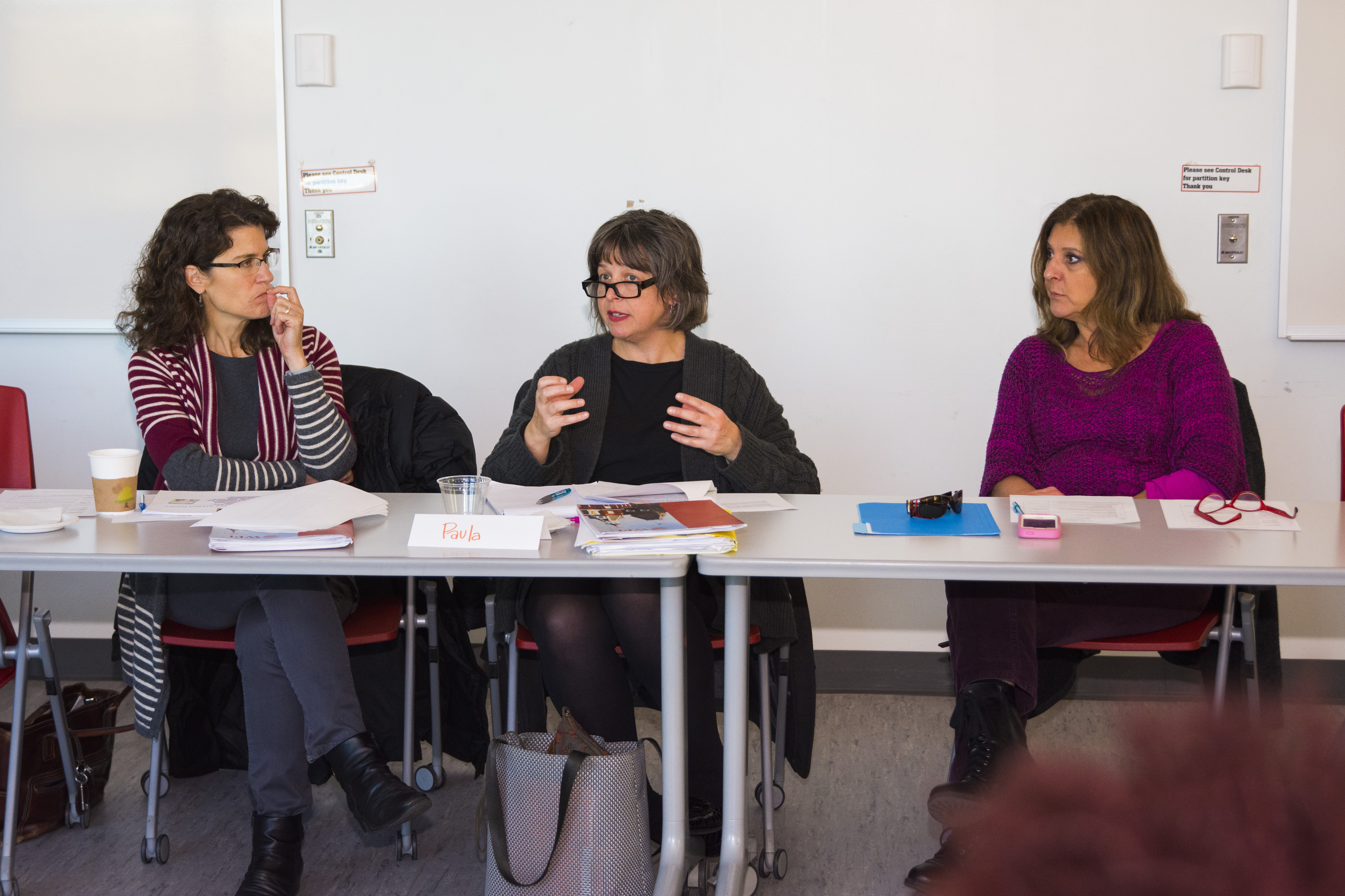 three women in a meeting at  a long table