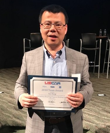 Professor Wang holds the USCAR Award certificate and looks into the camera
