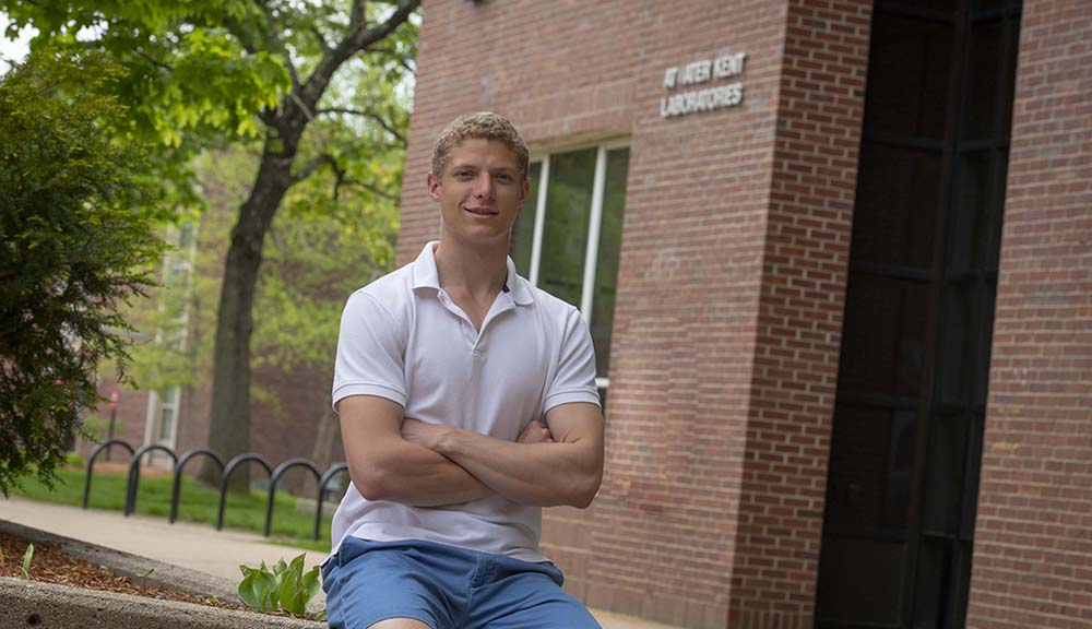 Matthew Adiletta smiles in front of a laboratory on campus.