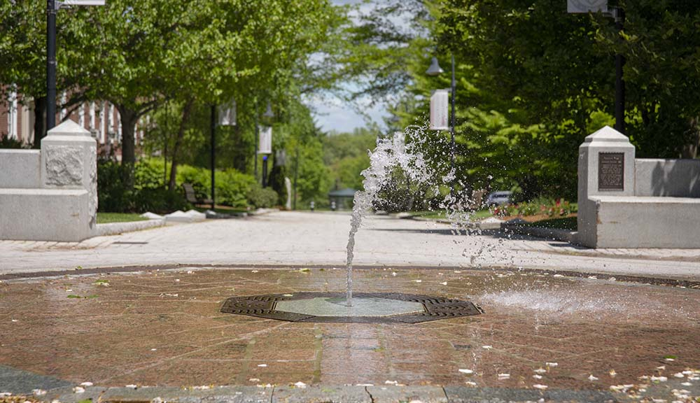 A shot of the fountain in the middle of campus with a blue sky and green trees in the background.