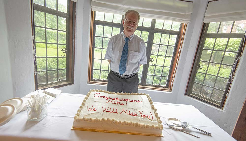 "Mike Dorsey stands behind a large cake that reads ""Congratulations Mike! We'll miss you!"" in Higgins House."