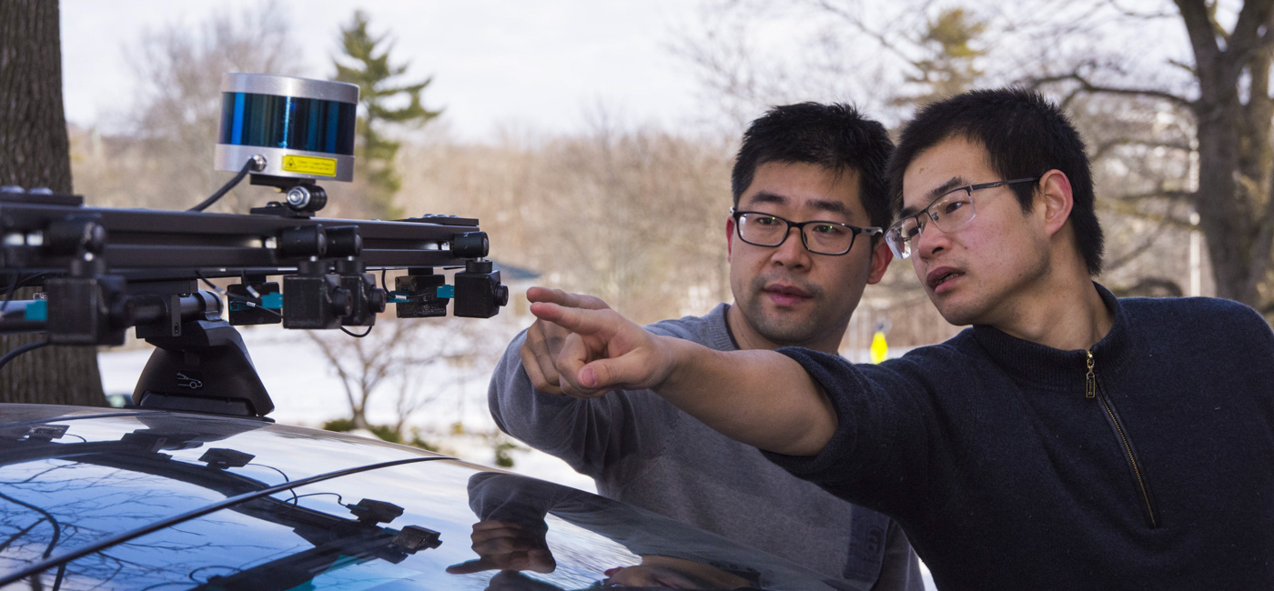 Two WPI students examining a large sensor array installed on the roof of a car