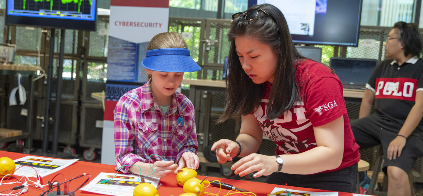 A student shows a young girl how to generate electricity from lemons with a cybersecurity poster in the background