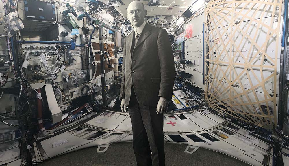 A black and white cardboard cutout of Robert Goddard is placed inside a replica of the interior of the International Space Station.