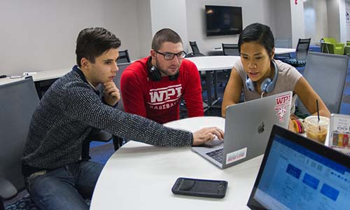 3 students sitting at a table conversing over something on a laptop.